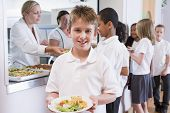 picture of tweeny  - Students in cafeteria line with one holding his healthy meal and looking at camera  - JPG