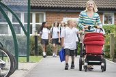 stock photo of tweeny  - Woman and young boy pushing a stroller outside school with students in background  - JPG