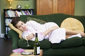 stock photo of housecoat  - Young woman lying on sofa smoking and drinking wine - JPG