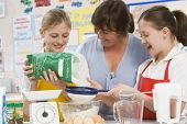 Teacher Helping Pupils In School Cookery Lesson