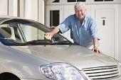 Постер, плакат: Старший мужчина мыть свою машину вне своего дома