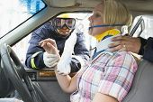 stock photo of neck brace  - Two firemen helping a woman in neck brace breathe with oxygen mask - JPG