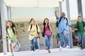 picture of pre-adolescents  - Six students running away from front door of school excited - JPG