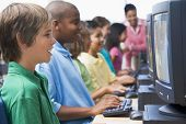 picture of school child  - Six children at computer terminals with teacher in background  - JPG