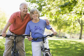 stock photo of older men  - Senior couple on bicycles - JPG