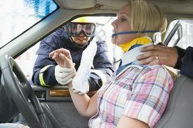stock photo of neck brace  - Two firemen helping a woman in neck brace breathe with oxygen mask - JPG