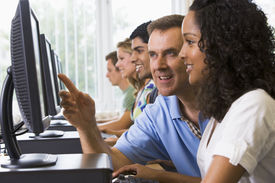 stock photo of student teacher  - Four students sitting at computer terminals with teacher helping one of them  - JPG