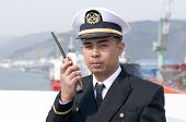 stock photo of lng  - Navigation officer is talking by VHF radio looking ahead on the navigation bridge of ocean ship - JPG