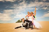 foto of contortionist  - A group of young acrobatic contortionists pose supporting each other in a desert scene - JPG