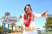 Elvis look-alike impersonator man and Las Vegas sign on the strip. People having fun and Viva Las Ve