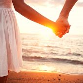 Love - romantic couple holding hands, beach sunset. Lovers or newlywed married young couple in roman