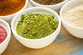 picture of moringa oleifera  - moringa leaf powder in a small bowl among other super fruit powders - JPG