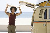 picture of campervan  - Portrait of a mixed race man with surfboard on head by camper van - JPG