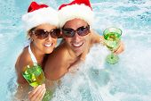 stock photo of tub  - Happy christmas santa couple in hot tub - JPG