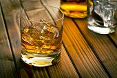 whiskey in glass with ice on wooden table