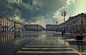 foto of pedestrian crossing  - Pedestrian crossing and big plaza at city center under cloudy sky at rainy day in Cuneo - JPG