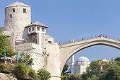 MOSTAR, BOSNIA AND HERZEGOVINA - AUGUST 10, 2012: Tourists on the Old Bridge with mosque in the back