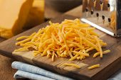 picture of shredded cheese  - Organic Shredded Sharp Cheddar Cheese on a Cutting Board - JPG