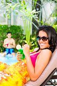 Asian woman tanning at pool on sun lounger drinking cocktails