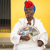 HAVANA,CUBA - JANUARY 20, 2014:Old black lady smoking a huge cuban cigar and wearing a typical dress