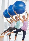image of pilates  - Happy fitness class and instructor doing pilates exercise with fitness balls in bright room - JPG