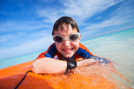 stock photo of boogie board  - Little boy on vacation having fun swimming on boogie board - JPG