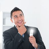 stock photo of southeast asian  - Southeast Asian businessman holding an illuminated light bulb - JPG