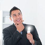 stock photo of southeast asian  - Southeast Asian businessman holding an illuminated light bulb - JPG
