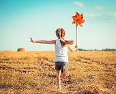 picture of windmills  - cute little girl in summer day holds windmill in hand - JPG