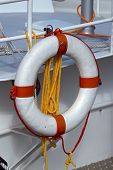 stock photo of life-boat  - Life preserver and rope hanging from the railing of a boat - JPG