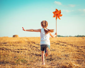 foto of windmills  - cute little girl in summer day holds windmill in hand - JPG