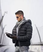picture of down jacket  - Handsome unshaven trendy man in winter fashion wearing a thick jacket - JPG