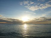 stock photo of waikiki  - Dramatic Sunset over the clouds and reflecting on the Pacific ocean on the water of Waikiki as boat sails in water on Oahu Hawaii - JPG