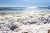 stock photo of sunrise  - sand sea beach and blue sky after sunrise and splash of seawater with sea foam and waves - JPG
