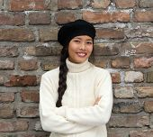 stock photo of beret  - Close up portrait of a smiling young woman wearing beret hat - JPG