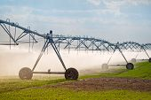 stock photo of sprinkler  - Automated Farming Irrigation Sprinklers System in Operation on Cultivated Agricultural Field - JPG