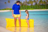 picture of mattress  - Little girl and young father with air mattress on beach vacation - JPG