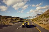 picture of road trip  - Rear view of couple driving in small car on open road - JPG