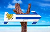 stock photo of negro  - Uruguay Flag wooden sign with beach background - JPG