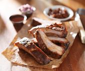 picture of spare  - grilled barbecued spare ribs with baked beans and coleslaw  on wooden cutting board - JPG