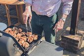 picture of braai  - A senior man is grilling pieces of chicken on a barbecue in a garden on a sunny day - JPG