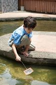 stock photo of fish pond  - Young boy enjoying a day catching and feeding fish in pond - JPG
