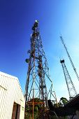 stock photo of mast  - Telecommunication mast with microwave link and TV transmitter antennas over a blue sky - JPG