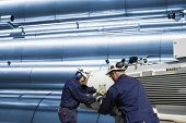 stock photo of pipeline  - two oil workers with machinery - JPG
