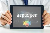 picture of autism  - The word asperger and autism awareness jigsaw against medical biology interface in black - JPG