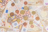 image of fifties  - Closeup of different coins over fifty notes background - JPG