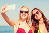 stock photo of two women taking cell phone  - summer vacation - JPG