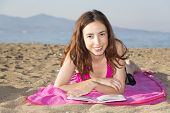 foto of sunbathers  - Caucasian woman sunbathing on the beach and reading a book - JPG