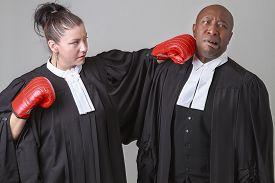 image of toga  - caucasian woman wearing a lawyer toga punching a black man wearing a lawyer toga - JPG