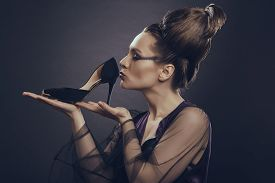 picture of sympathy  - Fashion addicted sensual woman with loop of hair gently holding and kissing her new high heel shoe over dark background - JPG